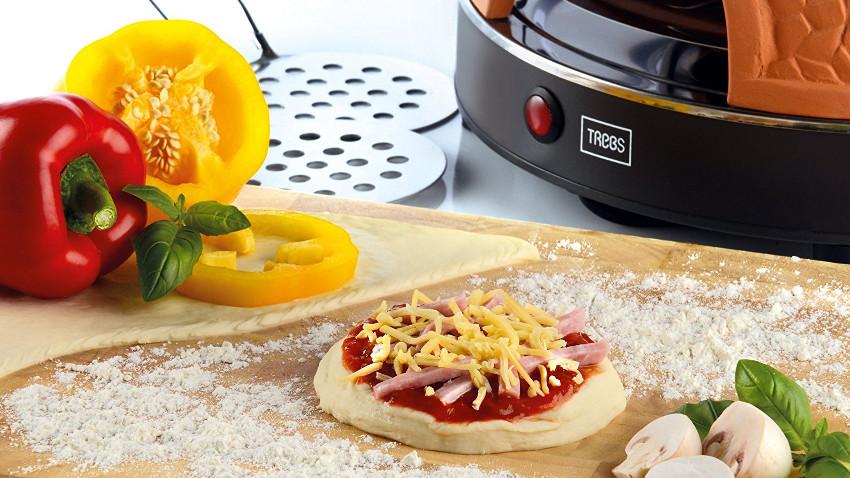Kleine Mini-Pizza in der Mitte des Bildes. Am Rand steht eine Pizzarette und eine gelbe und rote Paprika