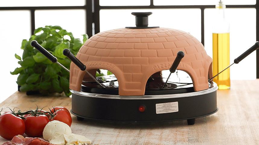 Pizzarette mit 4 Pfännchen, steht auf einem braunen Tisch. Im Hintergrund steht Oliven-Öl und Basilikum