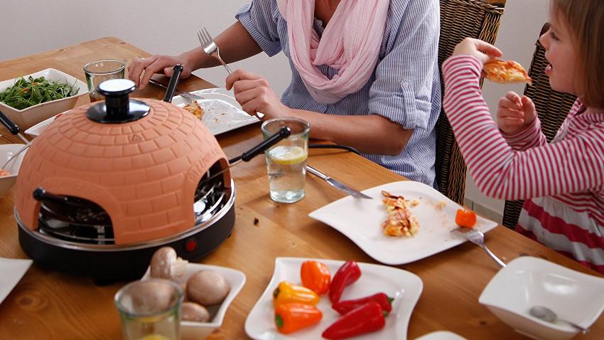 Originale Pizzarette auf einem braunen Tisch mit vielen passenden Zutaten drum herum