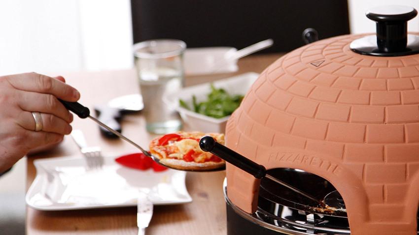 Pizzarette von Tefal in de rechten Bildhälfte. Links werde gerade eine Pizza auf dem Ofen genommen